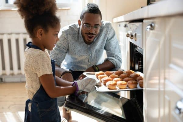 Best Nonstick Bakeware   photo of young girl pulling baking sheet from oven as father watches