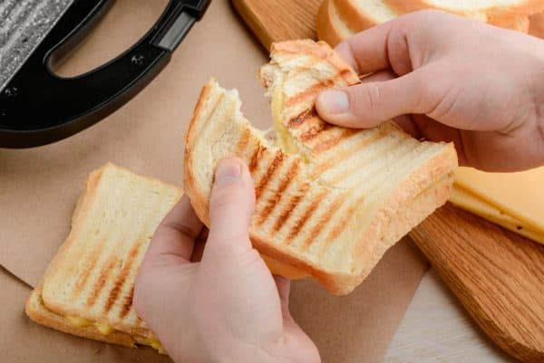 Best Sandwich Maker | photo of hands tearing a hot grilled cheese sandwich