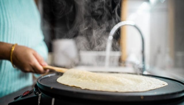best pancake maker | photo of woman flipping pancake on electric cooker
