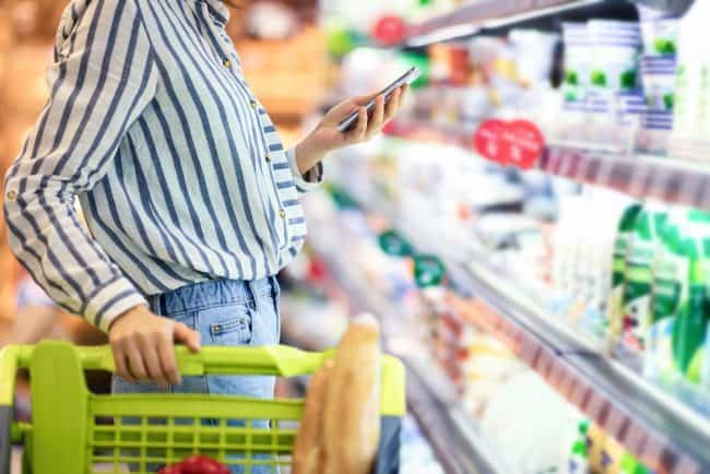 meal planning made easy   Young woman with cellphone shopping in supermarket