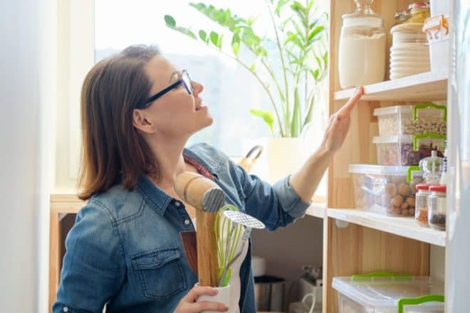 How to stock a pantry for the first time | photo of woman studying pantry shelves
