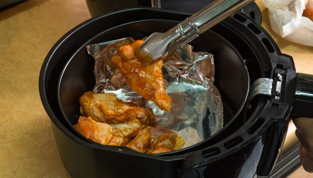 can you put aluminum foil in an air fryer? | photo of air fryer with chicken cooking in foil