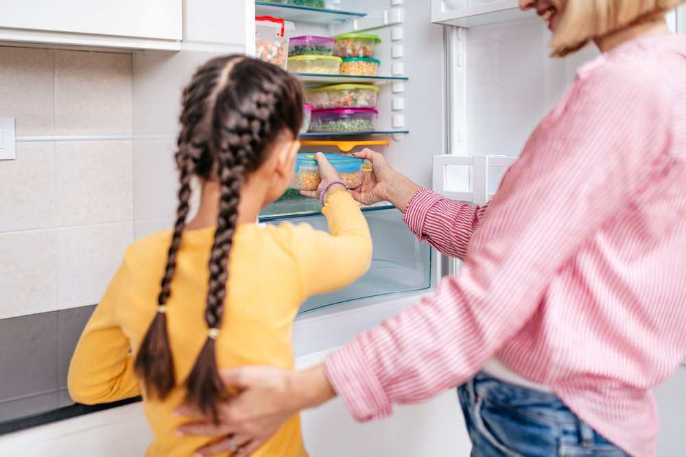 Photo of mother and daughter filling family freezer