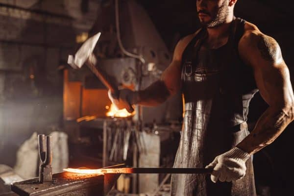 How to Unwarp a Pan | photo of traditional blacksmith in dark forge