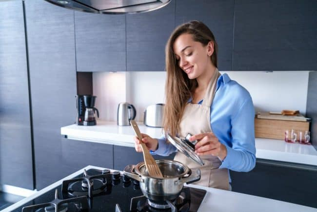 Photo of woman cooking using one of best pots and pans for gas stove