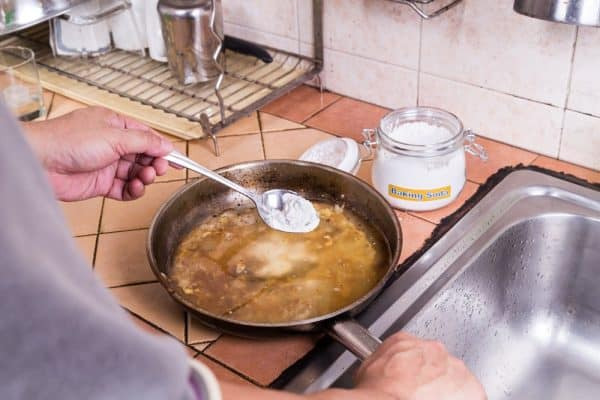 Photo using Baking soda to soak burnt pans