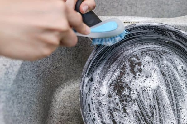 How to clean burnt calphalon pans | photo woman washing pan with bristle brush in sink