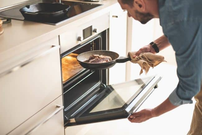 Are T-fal Pans Oven Safe | photo of  man holding frying pan while opening oven door
