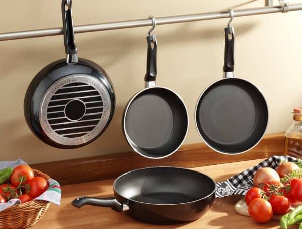 Saute Pan vs Fry Pan   photo of black pans hanging in modern kitchen