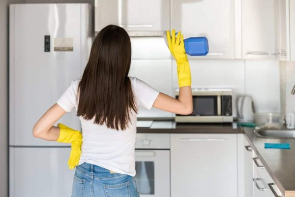 How to Clean an Air Fryer | photo of rear view of woman cleaning kitchen
