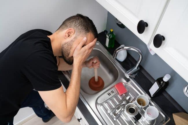 How to Dispose of Cooking Oil at Home | photo of man palming face as trying to use plunger on sink drain