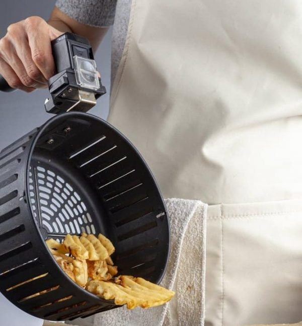 How to Clean an Air Fryer | photo of cook pouring out basket from air fryer